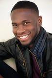 Attraktiver junger Mann, der in der schwarzen Lederjacke lächelt Lizenzfreies Stockbild