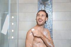 Attraktiver junger Mann, der Dusche mit Seife nimmt lizenzfreie stockbilder