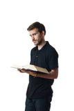 Attraktiver junger Mann, der ein Buch liest Stockbild