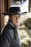 Attraktiver junger Mann, der einen schwarzen Cowboyhut trägt Stockbild