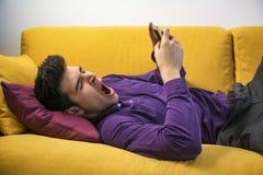 Attraktiver junger Mann, der Handy verwendet und gähnt Lizenzfreie Stockfotos
