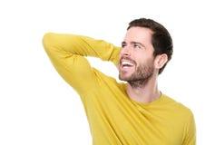 Attraktiver junger Mann, der mit der Hand im Haar lächelt Stockfotografie