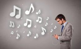 Attraktiver junger Mann, der Musik mit Musical singt und hört Lizenzfreies Stockbild