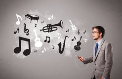 Attraktiver junger Mann, der Musik mit Musical singt und hört Stockfoto