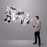 Attraktiver junger Mann, der Musik mit Musical singt und hört Stockfotografie
