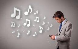Attraktiver junger Mann, der Musik mit Musical singt und hört Stockbilder