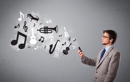 Attraktiver junger Mann, der Musik mit Musical singt und hört Stockbild