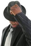Attraktiver junger Mann in der Nadelstreifen-Klage, die seinen Hut spitzt Lizenzfreie Stockbilder