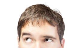 Attraktiver junger Mann, der oben auf Weiß getrennt schaut Stockbilder