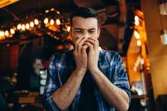 Attraktiver junger Mann, der seine Nase durchbrennt Stockfoto