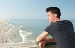 Attraktiver junger Mann, der am Strand lächelt Stockbilder