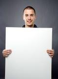 Attraktiver junger Mann, der weißen Vorstand anhält Stockfoto