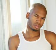 Attraktiver junger Mann, der zu Hause durch Fenster aufwirft Lizenzfreies Stockbild