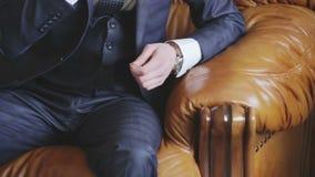 Attraktiver junger Mann in einer Klage, die auf einer Retro- Couch sitzt stock video