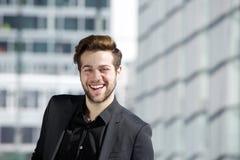 Attraktiver junger Mann mit Bart lächelnd in der Stadt Stockfoto