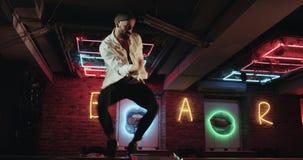 Attraktiver junger Mann mit dem Bart, der Energie- auf dem Tisch Stange im Nachtklub mit dem erstaunlichen Flackern tanzt, beleuc stock video footage