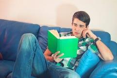 Attraktiver junger Mann mit dem Buch auf einer Couch lizenzfreies stockbild