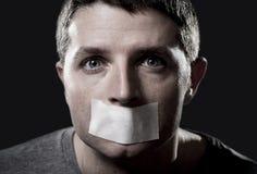 Attraktiver junger Mann mit dem Mund versiegelt auf Panzerklebeband, um ihn am Sprechen zu hindern stockbilder