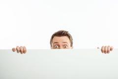 Attraktiver junger Mann versteckt sich hinter weißer Wand Stockfoto