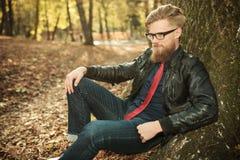 Attraktiver junger Modemann, der im Park sitzt Lizenzfreies Stockbild
