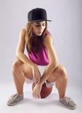 Attraktiver junger weiblicher Basketball-Spieler, der auf Ball sitzt Lizenzfreies Stockfoto