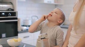 Attraktiver kaukasischer Junge Liltle mit großen blauen Augen Käse essend während c die Küche Junge Mutter und nettes schönes stock video
