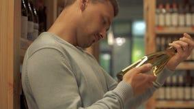 Attraktiver Kerl überprüft sorgfältig die Zusammensetzung auf dem Aufkleber einer Weißweinflasche im Spirituosenladen Weinflasche stock video