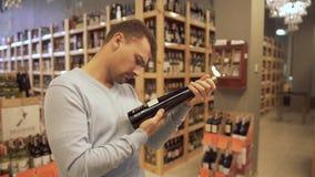 Attraktiver Kerl überprüft sorgfältig die Zusammensetzung auf dem Aufkleber einer Weinflasche in einer Weinhandlung Weinflaschen  stock video footage
