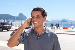 Attraktiver Kerl bei Rio de Janeiro, der am Telefon spricht Stockbild