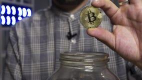 Attraktiver Kerl Blogger l?sst gro?es Gold-bitcoin in Glasgef?? vor Kamera fallen stock video footage