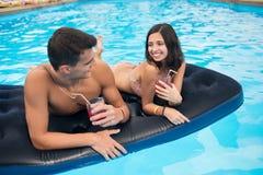 Attraktiver Kerl der Nahaufnahme und lächelndes ein Mädchen, das auf einer Matratze im Pool mit Cocktails liegt Lizenzfreies Stockfoto