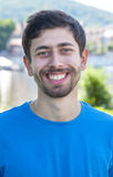 Attraktiver Kerl mit Bart und blauem Hemd ist glücklich Stockfotografie