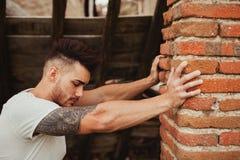 Attraktiver Kerl nahe bei einer Backsteinmauer Stockbilder