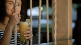 Attraktiver lächelnder Brunette spielt auf Schwingen mit Cocktail in ihren Händen am Abend Junges schönes Mädchen ist stock video footage