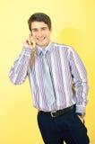 Attraktiver lächelnder Geschäftsmann mit einem Mobiltelefon stockfotos