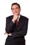 Attraktiver lächelnder Mann in der Klage mit der Hand zum Gesicht Lizenzfreie Stockfotos