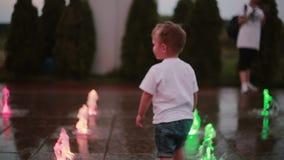 Attraktiver laufender Abflussrinnenbrunnen des kleinen Jungen und rührende Wasserstrahlen Kind, das Spaß am heißen Sommertag hat stock video