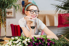 Attraktiver lächelnder Florist der jungen Frau, der im Blumenladen arbeitet Lizenzfreies Stockfoto