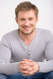 Attraktiver lächelnder Mann, der auf weißem Hintergrund sich entspannt Stockbilder