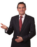 Attraktiver lächelnder Mann in der Klage Willkommen gestikulierend Lizenzfreie Stockbilder