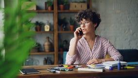Attraktiver Mädchendesigner spricht auf dem Smartphone, der bei Tisch sitzen und dem rührenden Briefpapier, das zu Hause arbeitet stock video footage