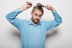Attraktiver männlicher Friseur schier sich mit Scheren und Kamm stockfotos
