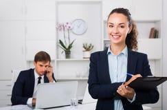 Attraktiver Manager der jungen Frau, der Pappe im Büro hält stockbilder