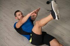 Attraktiver Mann, der Abdominal- Übung auf Boden durchführt Stockfoto