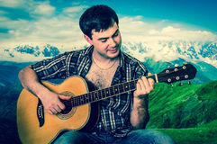 Attraktiver Mann, der Akustikgitarre - Retrostil spielt Stockfotografie