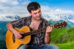 Attraktiver Mann, der Akustikgitarre spielt Lizenzfreie Stockfotografie