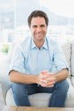 Attraktiver Mann, der auf der Couch lächelt an der Kamera sitzt Stockfotos