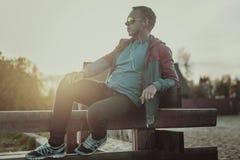 Attraktiver Mann, der auf Strand am Abend sitzt Lizenzfreie Stockfotos