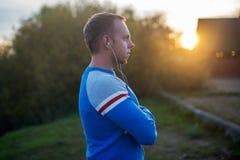 Attraktiver Mann, der auf Strand am Abend sitzt Stockfoto