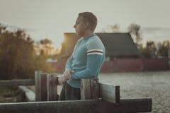 Attraktiver Mann, der auf Strand am Abend sitzt Lizenzfreie Stockfotografie